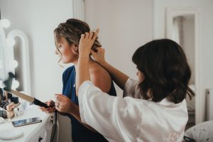Bride and bridesmaid getting ready