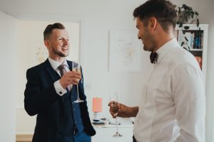 Best man and groom laughing