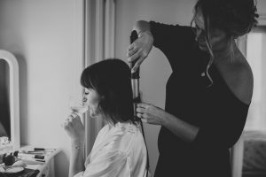 Bride having her hair done with champagne