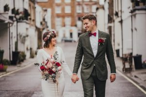 Bride and groom walking hand in hand in a mews