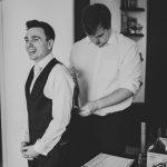 groom having his waistcoat done up