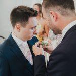 groom having button hole put on
