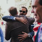 guest hugs groom before wedding