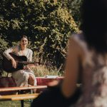 bridesmaid playing guitar before the wedding ceremony
