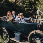 wedding guests having fun with classic car