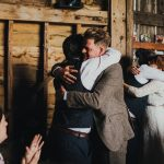 groom and bride hugging best men