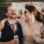 best man laughing with his girlfriend