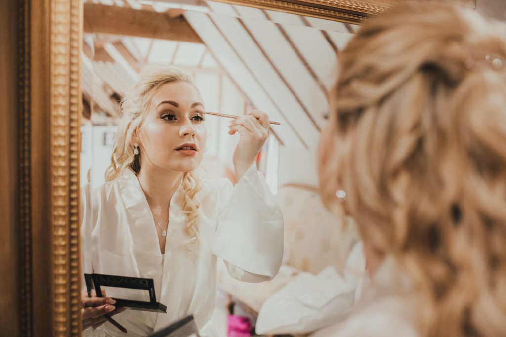 bride putting make up on in mirror