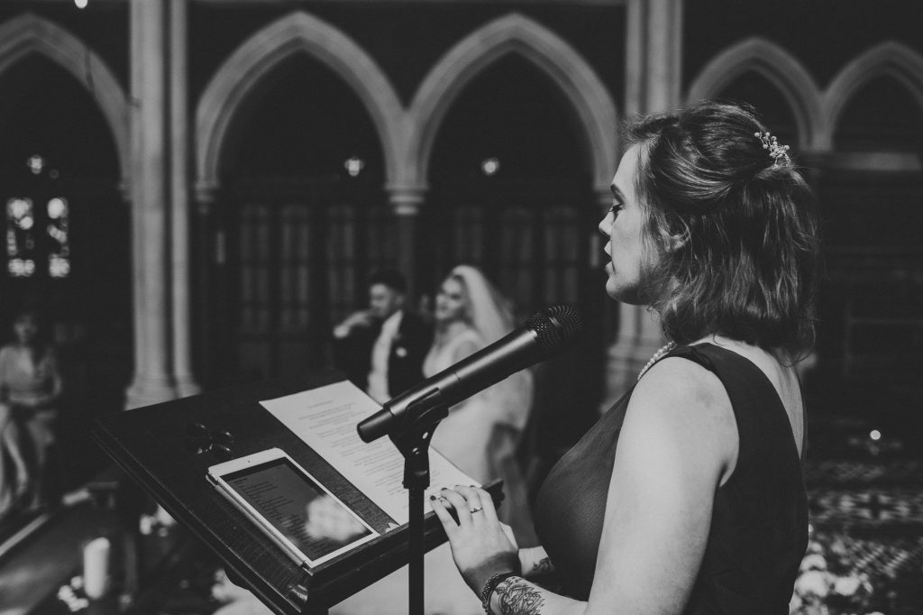 bridesmaid doing a reading at wedding ceremony