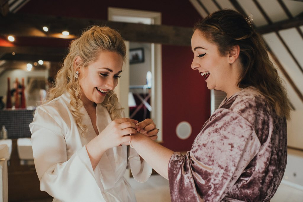 bride and bridesmaid putting on jewellery