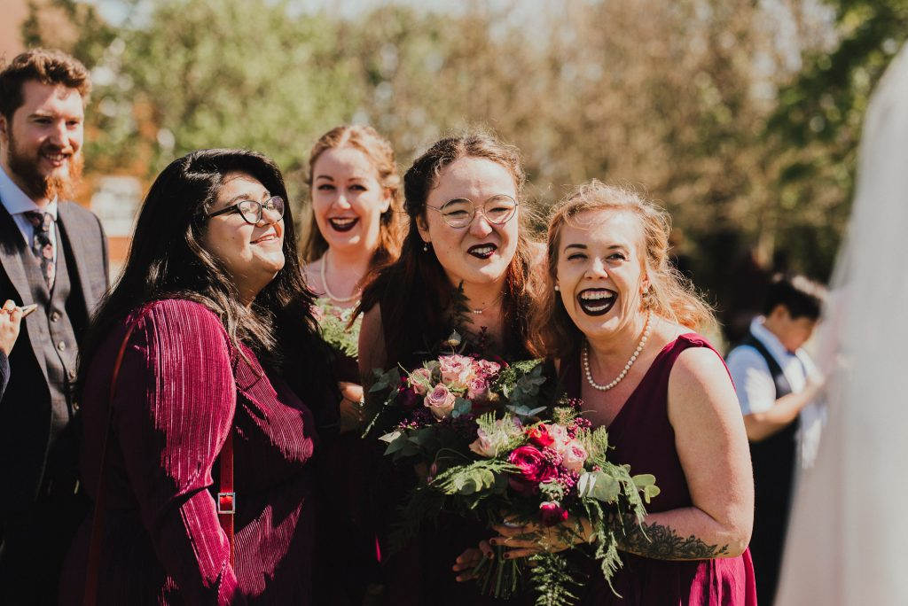 bridesmaids laughing after the wedding ceremony