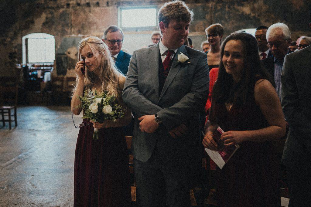 bridesmaid wipes a tear away
