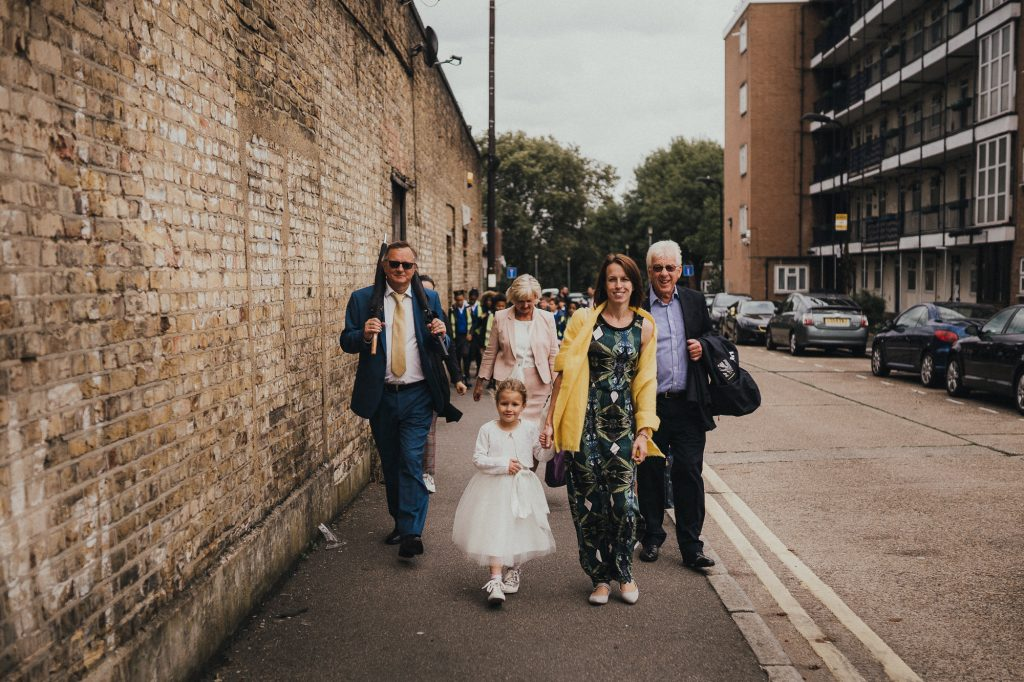 wedding guests walking down street