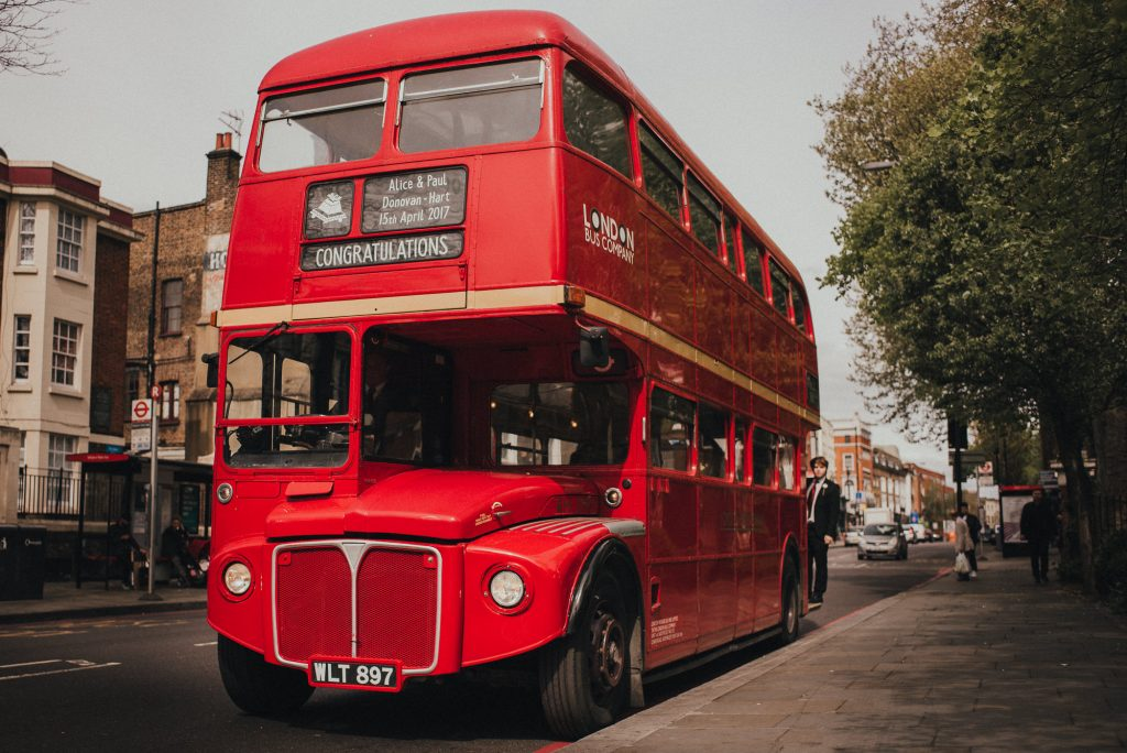 old red london bus arrives at wedding venue