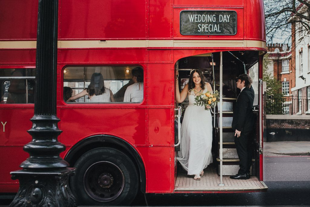 bride gets out of london bus at wedding venue
