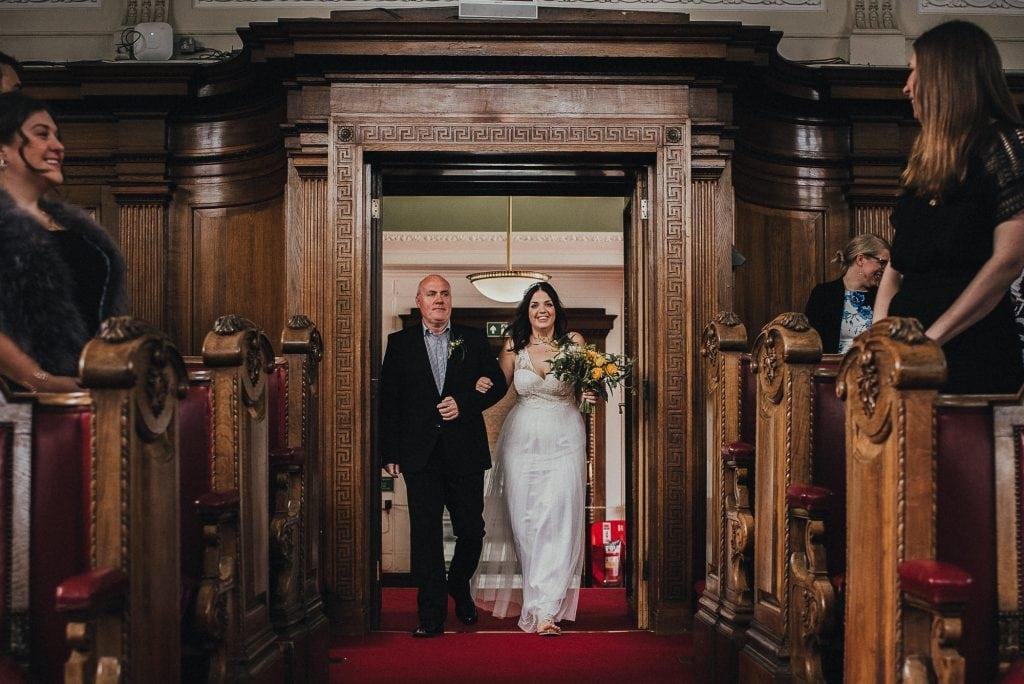 bridesmaid and father walk into ceremony venue