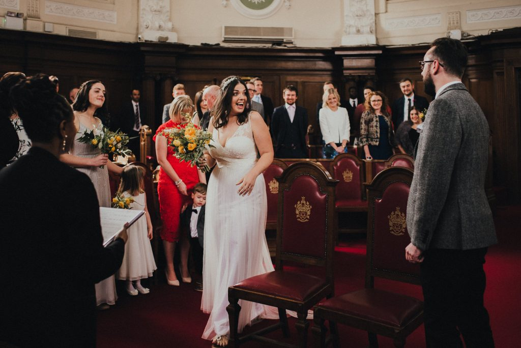 bride smiles at groom as she reaches top of the aisle