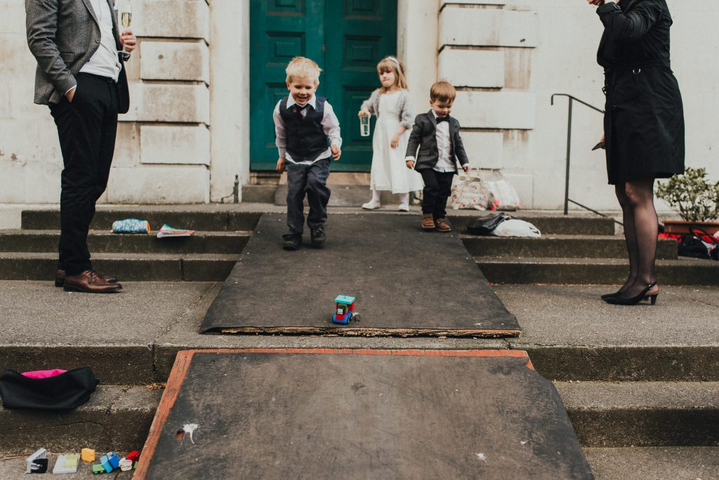 kids playing with cars during wedding reception