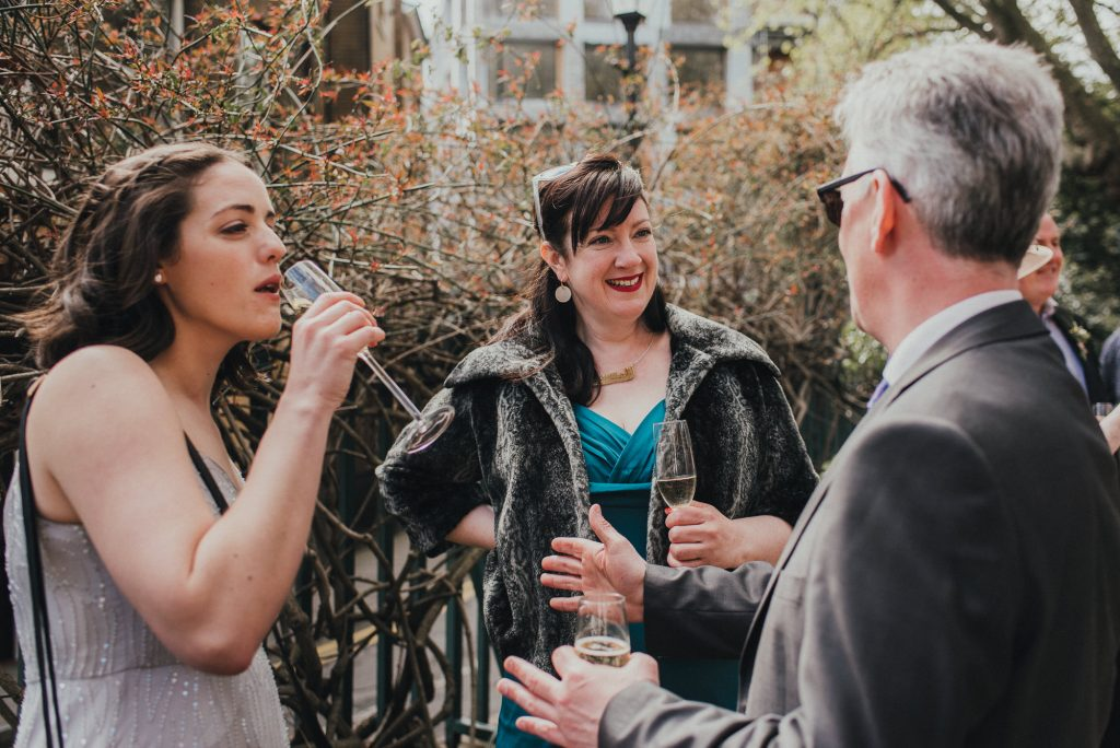 guest laughs at her husband's joke during reception