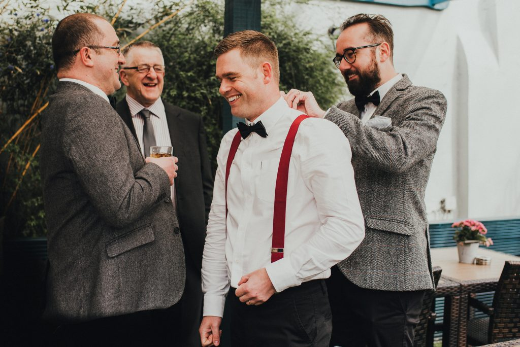 groom helping best man with bow tie