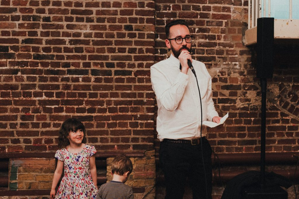 groom giving his speech with kids laughing