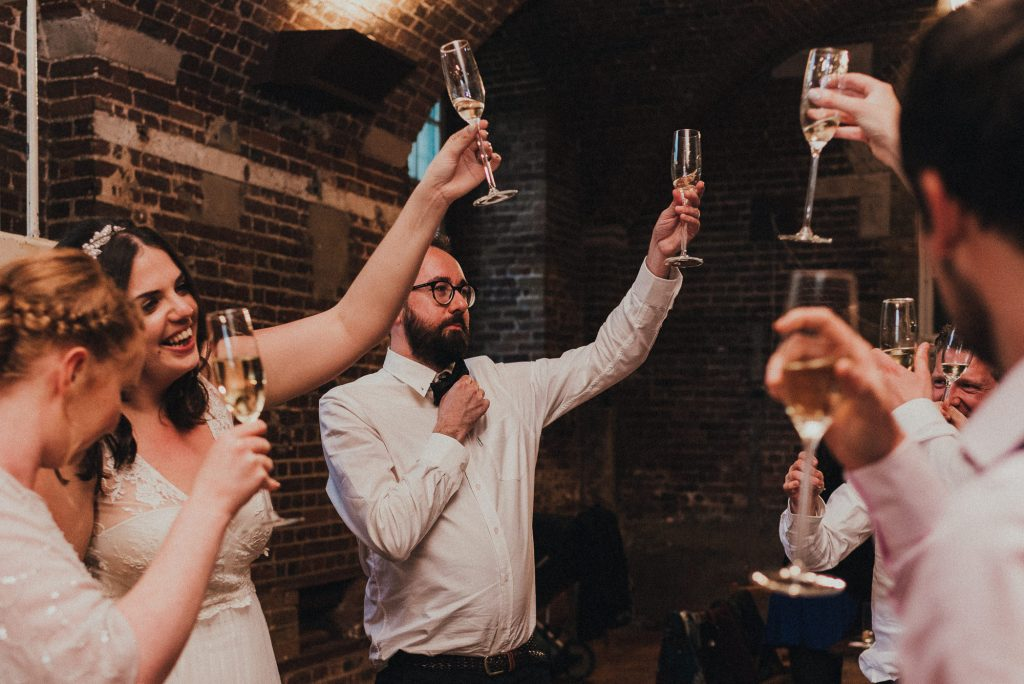 bride and groom and guests toasting