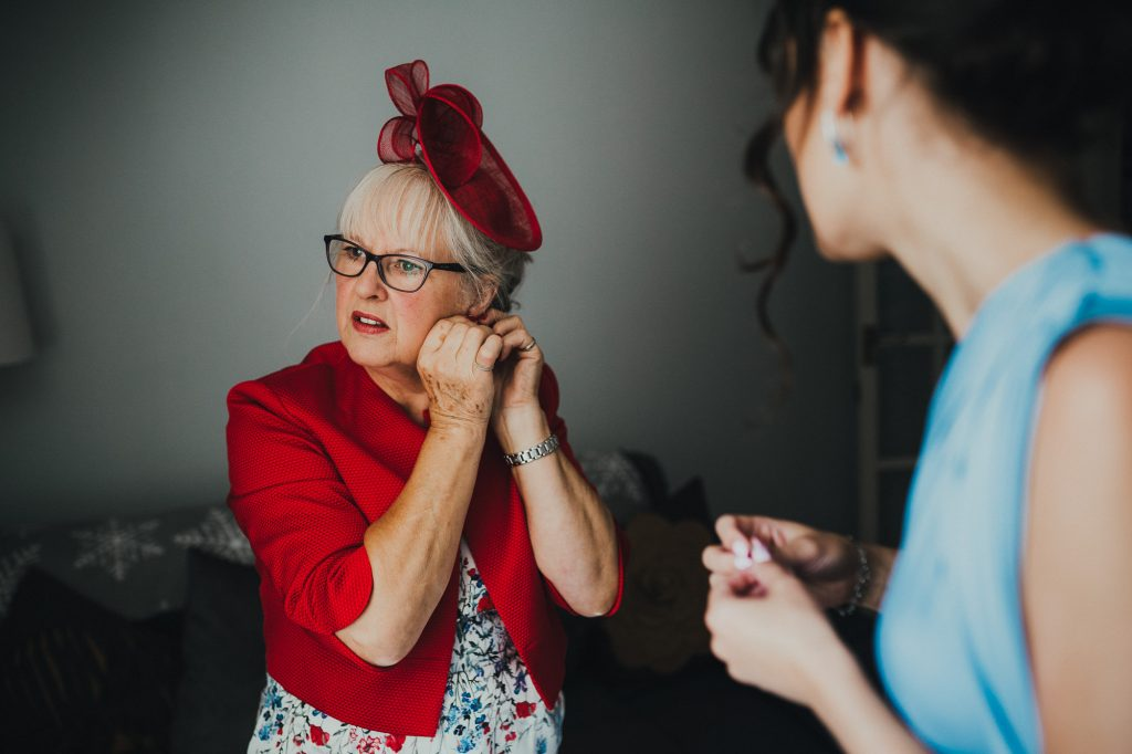 mother of the groom putting earrings on