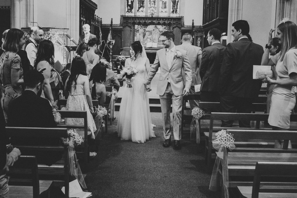 the bride and groom walking down the aisle
