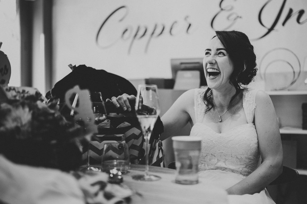 the bride laughing during the groom's speech