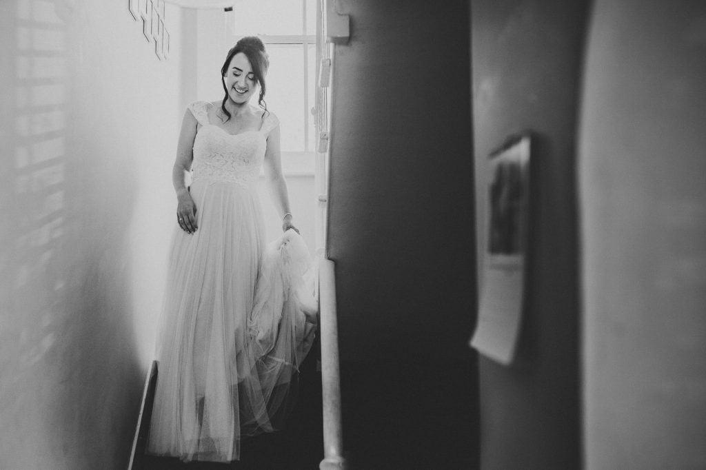bride walks down stairs in her dress