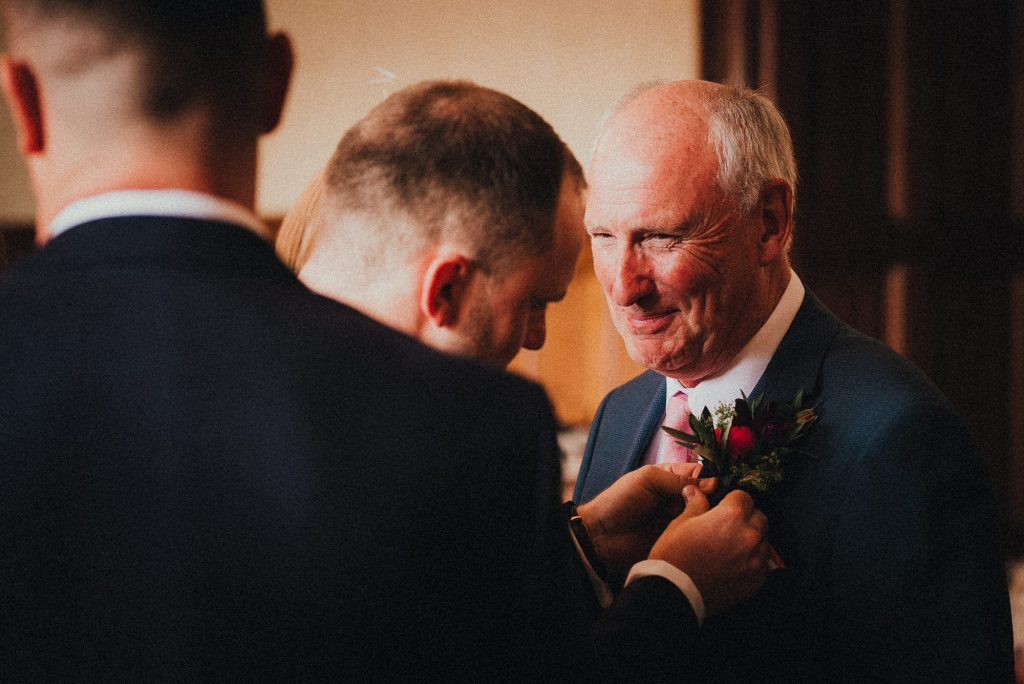 groom putting button hole on dad