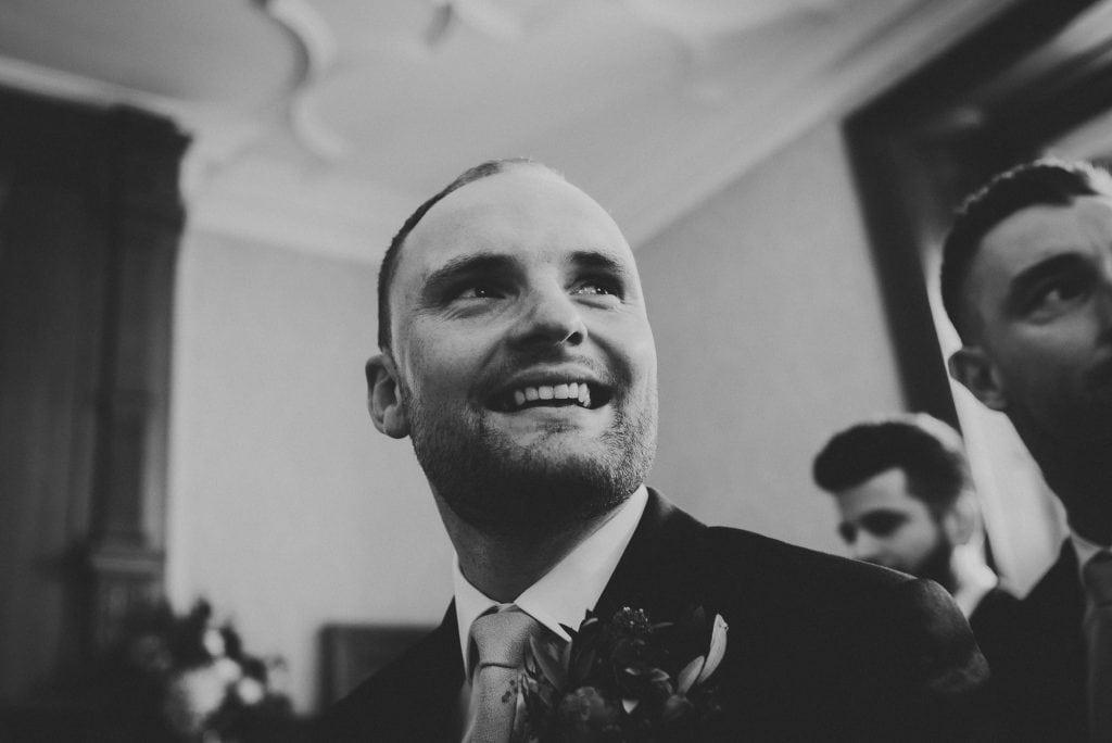 groom smiling as bride arrives
