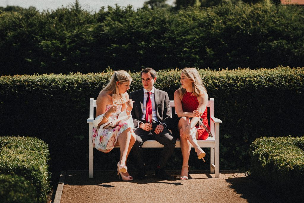 wedding guests sitting on a bench