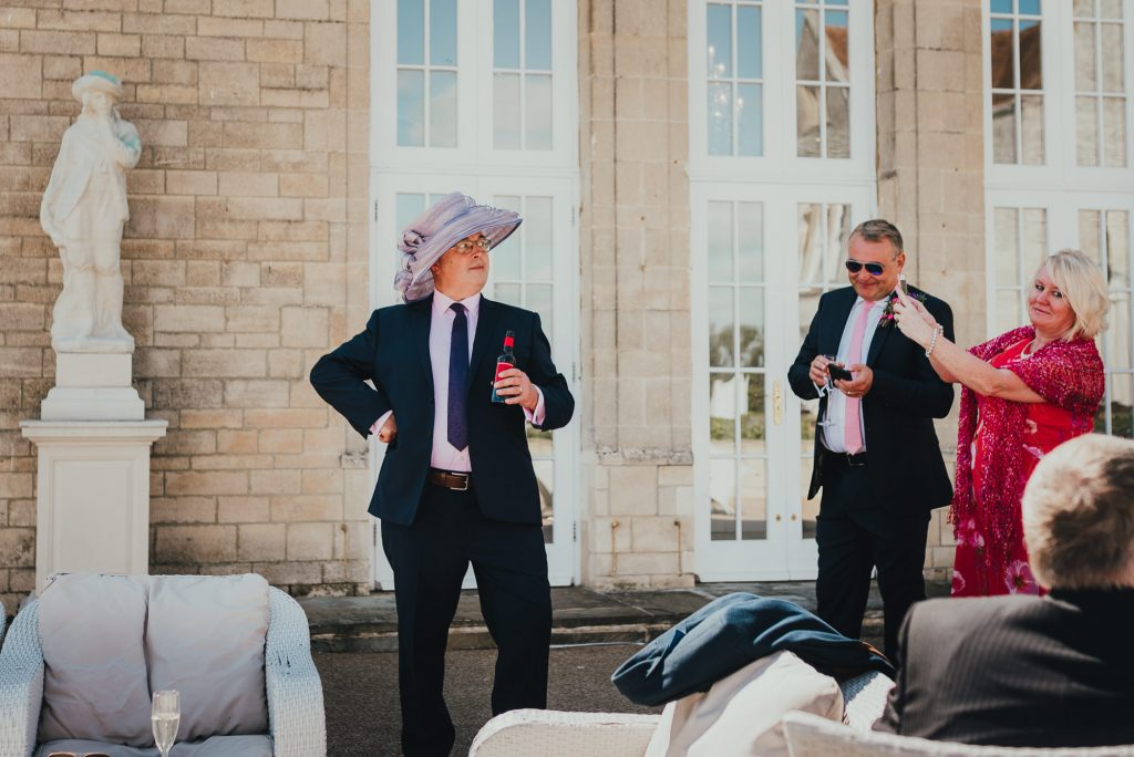 male wedding guest posing in mother of the bride's hat for a joke