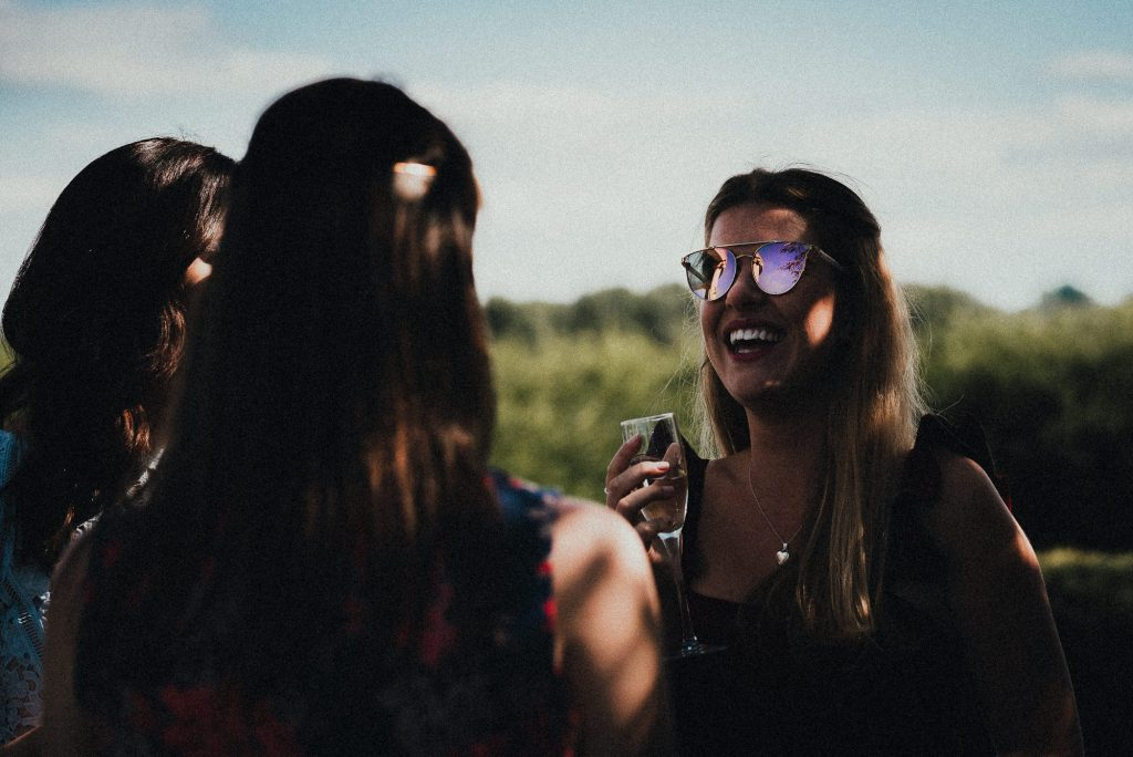 wedding guest with colourful sunglasses smiling