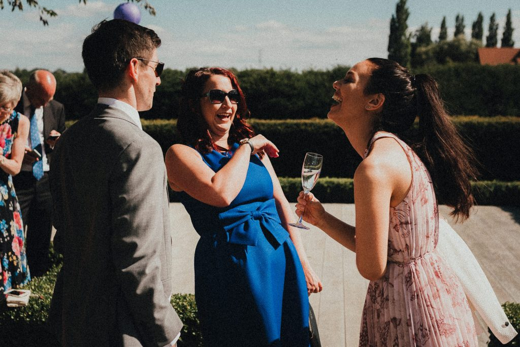 wedding guest laughing in the sun
